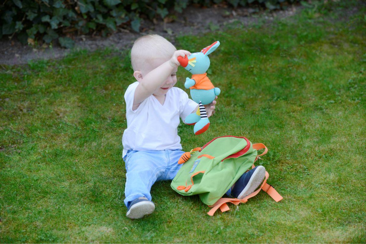 Copil ce se joacă cu Rucsac copii, cu jucărie senzorială iepuraș, Dolce